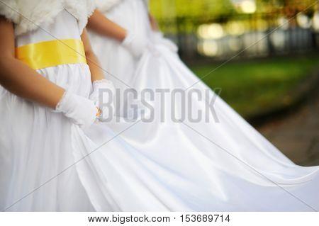 Little bridesmaids holding beautiful bride's wedding dress