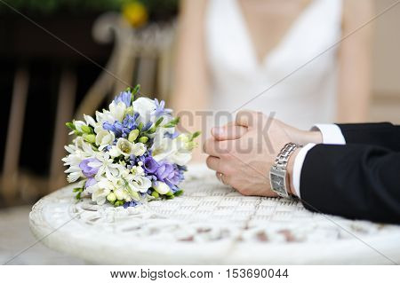 Groom's Hands And Wedding Bouquet