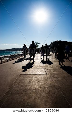 Walking people silhouettes. Sea coast many tourists. Soft vignetting effect.