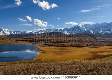 Bright picturesque autumn landscape with mountains covered with snow forest yellow larches and beautiful lake with reflections on a background of blue sky and clouds