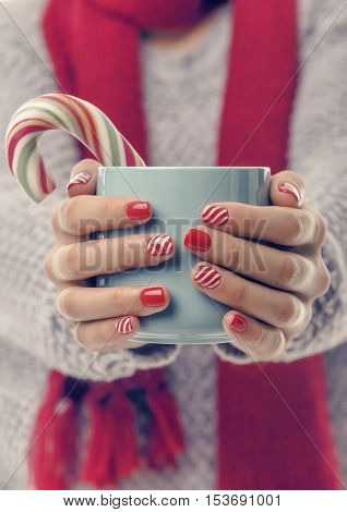 A cup with a drink and a Christmas candy in the hands. Close-up. Toned photo.