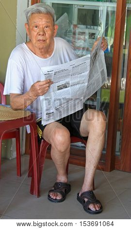 Vinh, Vietnam - May 30, 2015: old man is reading newspapers outdoor in Vinh, Vietnam