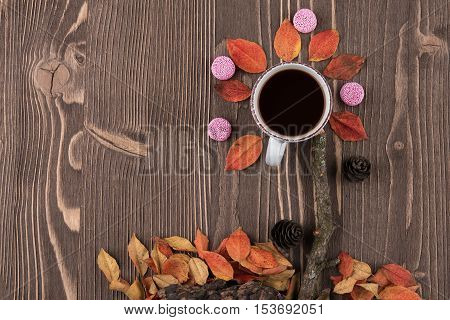 Red autumn leaves a Cup of coffee on wooden background