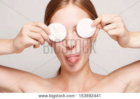 A picture of a happy woman cleaning her face with cotton pads over white background. Beautiful Face of Young Woman with Clean Fresh Skin close up. Youth and Skin Care Concept mouth and tongue