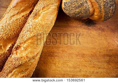 Assortment of baked French baguettes and poppy seed loaf on a wooden table