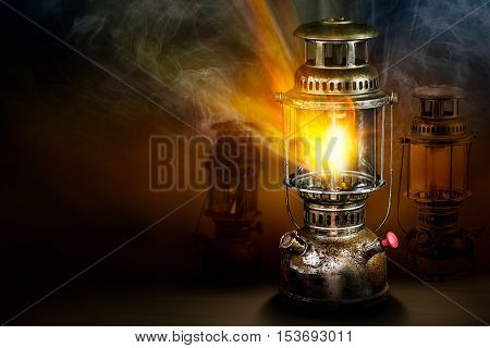 Beam of light and fire blaze with smoke from vintage rusty steel storm lantern on dark background