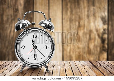 Modern silver metallic alarm clock on wooden table in vintage style