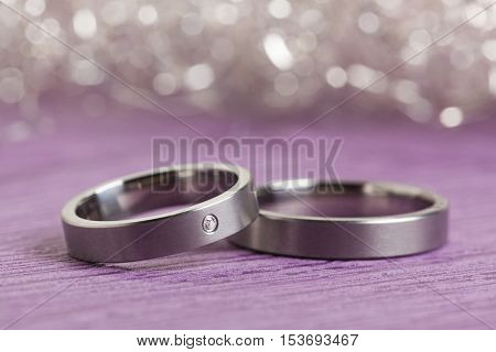 Silver engagement rings on purple surface with sparkling bokeh background