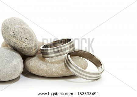 Closeup of wedding rings pair on pebbles, white background