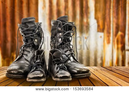 Combat boots for adult and kid on wooden floor and rusty galvanized iron wall in family concept