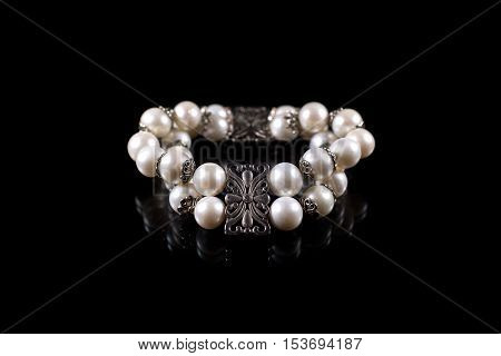 Bracelet of pearls isolated on black background