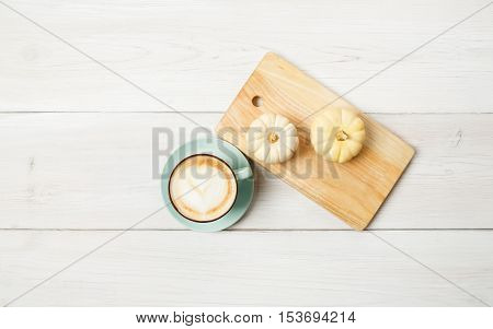 Pumpkin spice latte. Blue coffee cup with foam and small yellow pumpkins at white wood background. Autumn fall hot drinks, cafe and bar concept, top view with copy space