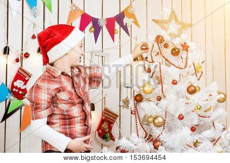 cute boy in red santa hat decorates a new year tree in decorated christmas room