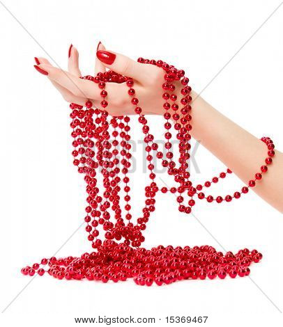 Woman hand holding red glassbeads. Isolated on white.