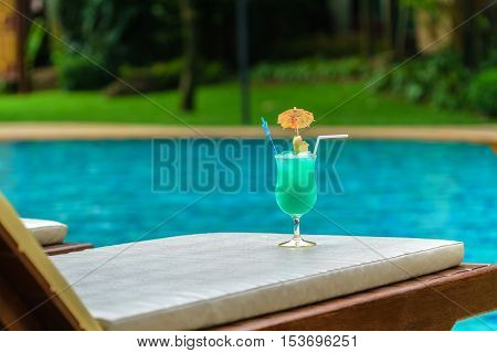 Glass of blue cocktail with decorated a umbrella at swimming pool in summer time Cocktail drink with copy-spaced