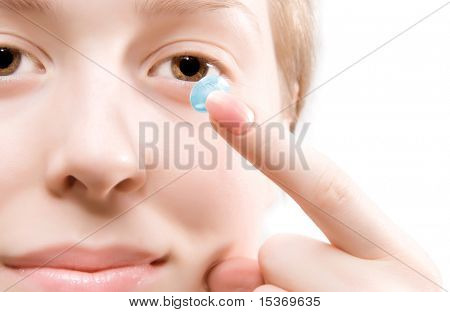 Young woman puting blue contact lens.