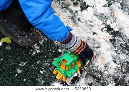 Part of the image of a small child that sits next to the first snow on the Playground and plays with red toy construction vehicle. Visible hand dressed in a glove a blue jacket black pants and boots.