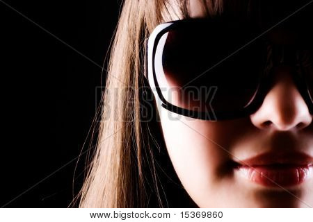 Woman in sunglasses portrait. Strong side light.