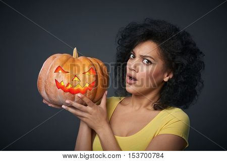 Scared woman holding Halloween pumpkin head jack lantern isolated over grey background