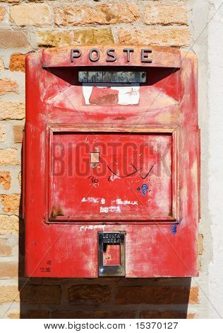 Old red Italian mail box on a wall.
