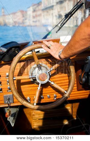 Standing at the wheel. Focus on male hand.