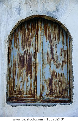 Metal, rusty window of an abandoned house