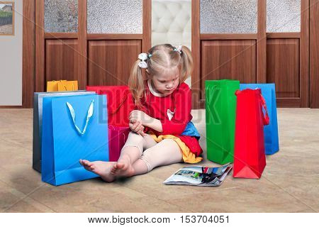 cute little girl sitting on the floor in the apartment. Lots of colorful shopping bags.