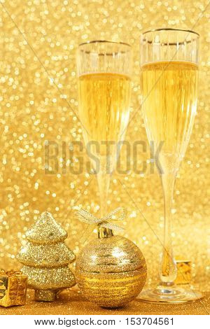 Two glasses of champagne with golden glitter lights on background