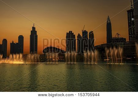 DUBAI, UAE - OCTOBER 13, 2016: A sunset night shot of the iconic dhow-shaped building of Dubai Opera with dancing fountains in front of it, which opened on 31st August 2016