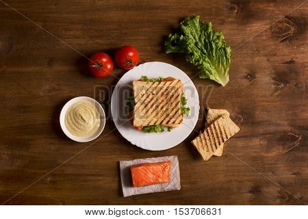Club sandwich prepared with fish on the wooden board. Top view