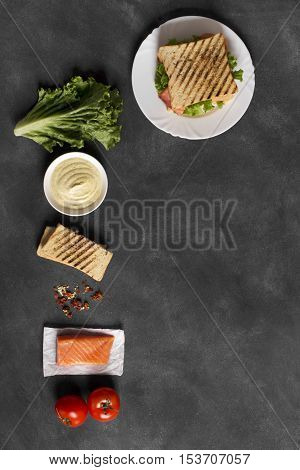 Club sandwich prepared with fish on the black chalkboard. Top view, vertical orientation