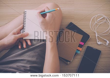 young man writing journal on notebook while sitting on floor with smartphone earphones and book beside him