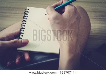 close-up on right hand while writing a journal in notebook