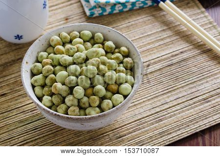 Wasabi peas a crunchy snack made with roasted green peas or soya beans coated with wasabi seasoning in a Japanese ceramic bowl
