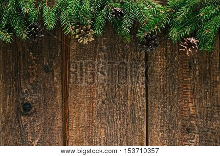 Christmas border of evergreen twigs on old brown wood. Overhead view