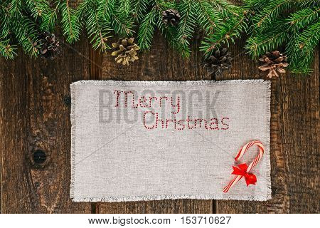 Christmas frame of evergreen twigs with candy cane on linen napkin with stitched text 'Merry Christmas'. Overhead view