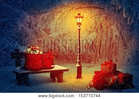 Lot of presents with Santa sacks in the park. Wooden bench and a shining lamp in the snowy night. Peaceful Christmas scene and winter holiday gifts. New Year celebration background.