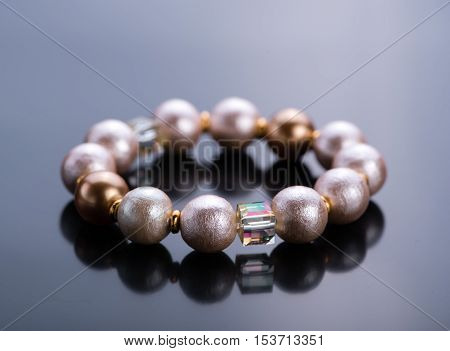 Pearl bracelet with crystals on a dark background. Beadwork.