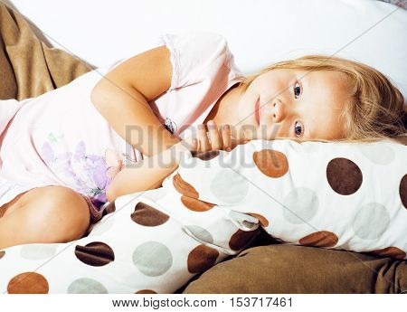 little cute blonde norwegian girl playing on sofa with pillows, crazy home alone, lifestyle people concept close up
