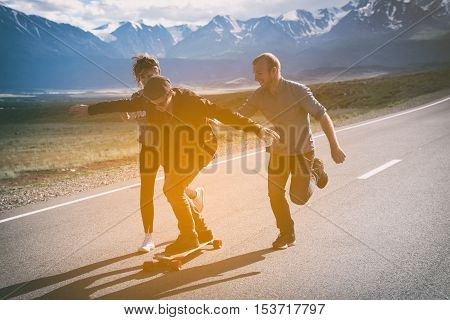 Group of friends run, laugh and having fun. The guy on longboard. Asphalt road.