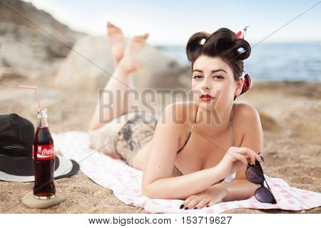 Baku, Azerbaijan - August 8, 2016: Pinup model with bottle of Coca Cola lying on sand near to the sea. Beach photo shoot with sexy girl in swimsuit.