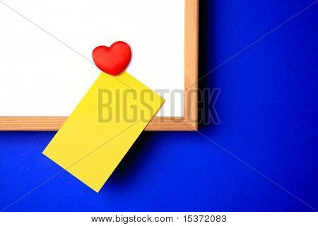 white-board with empty yellow post-it note and magnet in the form of a heart