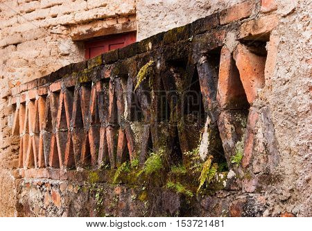 Partially moss covered X brick pattern set in stone wall