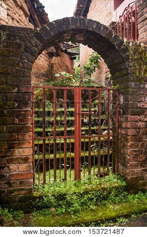 iron gate set in a brick archway with moss covered stairway leading up and is visible through it