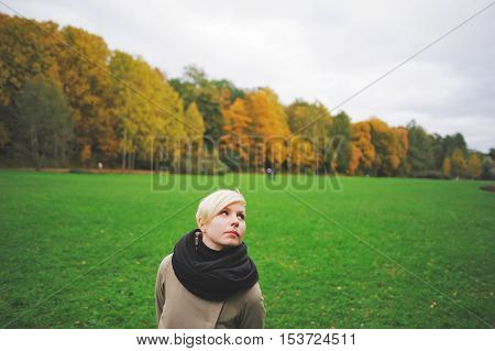Portrait of a young cute blonde girl in a city Park in autumn close-up.