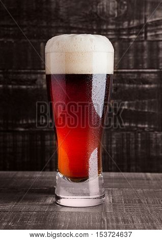 Glass of brown ale beer with foam on wooden background