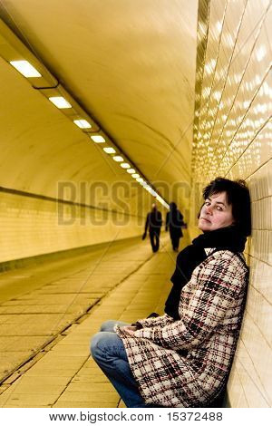 sad mature woman in a tunnel. two business-people in the background .personal editing