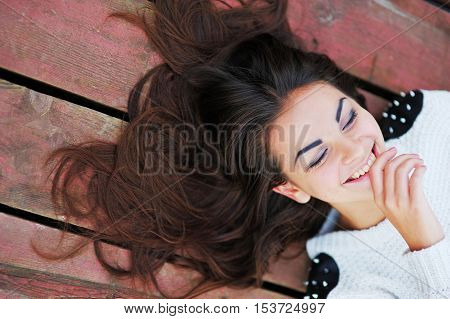 Beautiful girl with gorgeous hair lying on the boards with his eyes closed and smiling topic view closeup