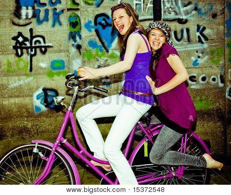 two girls having fun on a bicycle, personal editing ,green toning