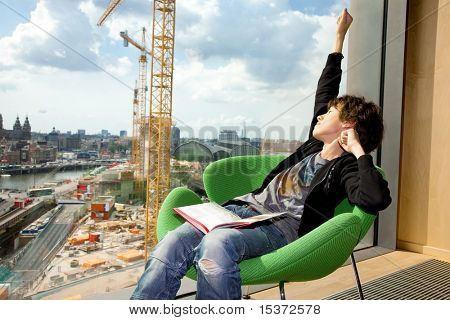 teenager reading a book in a library in front of a window overlooking the city .building his future